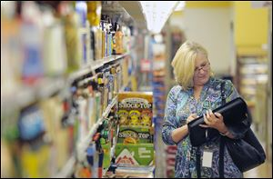 Caren Gaffney, an economic assistant with the U.S. Bureau of Labor Statistics, checks prices at a Virginia grocery store.