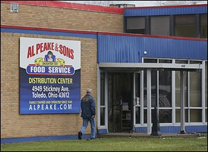 Daniel Dever, a special agent with the Internal Revenue Service, enters Al Peake & Sons Food Service, 4949 Stickney Ave. IRS and FBI agents raided the business Friday.