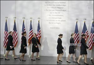 The U.S. Naval Academy Women's Glee Club walks under a passage from President John F. Kennedy's inaugural address before a ceremony on the 50th anniversary of his assassination at the John F. Kennedy library in Boston.