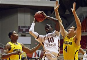 Florida State forward Okaro White, center, goes to the basket against Michigan's Glenn Robinson, left, and Mitch McGary during a NCAA college basketball game in San Juan, Puerto Rico, today.