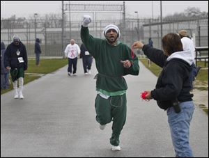 Toledo Correctional Institution prisoner Steve James lifts his arm in celebration of completing another lap during a 5K fund-raiser for the Susan G. Komen Foundation. He is reaching for a wristband from Case Manager Terrie Janowski to mark his laps.