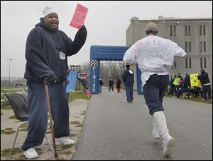Inmate Darrell Bruce  cheers on inmates participating in the run/walk for the Komen Foundation at the prison in North Toledo.