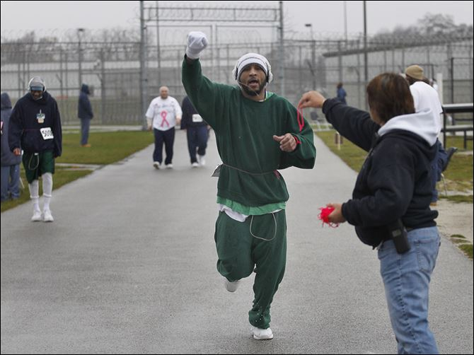 n7inmates Toledo Correctional Institution prisoner Steve James lifts his arm in celebration of completing another lap during a 5K fund-raiser for the Susan G. Komen Foundation. He is reaching for a wristband from Case Manager Terrie Janowski to mark his laps.