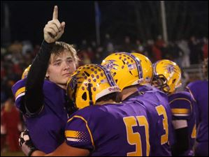Bryan's quarterback Austin Schimmoeller (12) raises his hand up as he is comforted by a teammate after losing to Kenton.