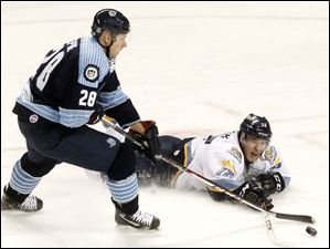 The Walleye's Travis Novak slides to get to the puck before Evansville's Guillaume Lepine.