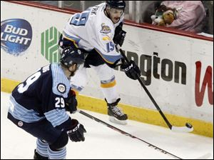The Walleye's Martin Frk gets to the puck before Evansville's Matt Krug.