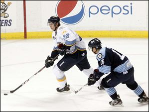 The Walleye's Russ Sinkewich takes control of the puck while Evansville's Nathan Moon plays defense.