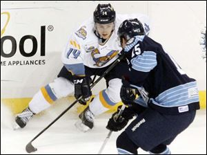 The Walleye's Joe Gleason and Evansville's Nathan Moon fight for the puck.