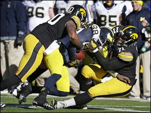 Michigan quarterback Devin Gardner (98) is sacked by Iowa defenders Christian Kirksey, left, and Carl Davis, right, during the second half, Saturday.