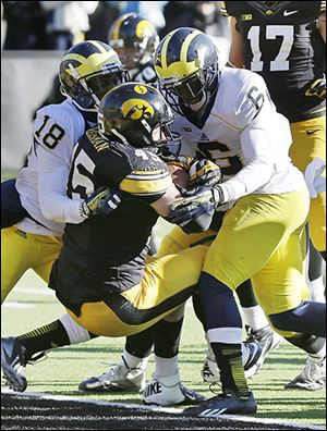 Iowa's Mark Weisman, center, scores a nine-yard TD between Michigan's Blake Countess, left, and Raymon Taylor.