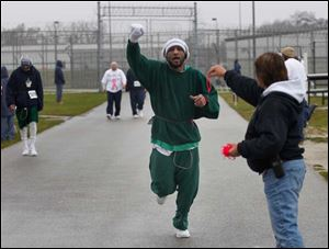 Toledo Correctional Institute inmate Steve James lifts his arm up in celebration of completing another lap during a 5K fundraiser for the Komen Foundation. He is reaching for a wristband marking his laps from case manager Terrie Janowski.
