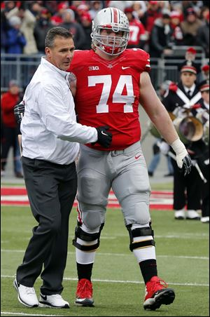 Ohio State's Jack Mewhort (74) is greeted by head coach Urban Meyer during senior day.