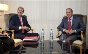 U.S. Secretary of State John Kerry, left and Russia's Foreign Minister Sergei Lavrov react, during a photo opportunity, prior to their meeting, in Geneva, Switzerland,  Saturday.