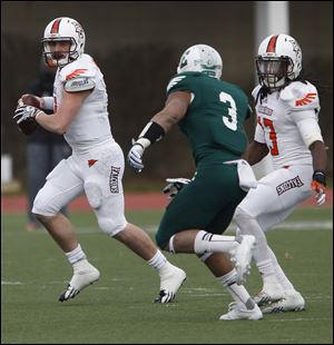 BG quarterback Matt Johnson seeks to evade Eastern Michigan's Donald Coleman. Johnson threw for 264 yards and three TDs.
