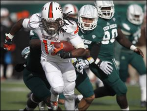 Bowling Green's Travis Greene is chased by Eastern Michigan defenders. Greene rushed for 126 yards and two touchdowns for BG.