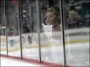 Erik Kenney Jr. watches police and fire hockey action up against the glass at the Huntington Center.