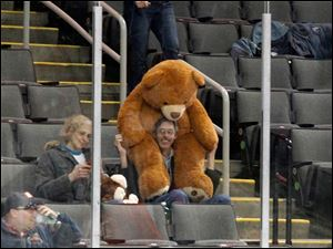 Ron Carroll, of Toledo, holds a big teddy bear on his head while watching the game with Bonnie Burns, left, during the