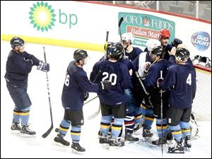 Toledo Police Department hockey players celebrate their win over the Toledo Fire Department team.