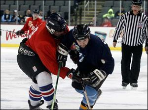Toledo Police player Rob Daunhauer (11), right, and Toledo Fire's Joe Camerato (19), left, fight for the puck.