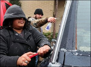 Samantha Hernandez scrapes ice off of the windows after Kenneth Fields sprays them with a concoction of vinegar and water to soften the ice on Saturday in Odessa, Texas.
