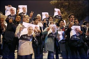 Iranians hold posters of President Hassan Rouhani as they cheer returning Iranian nuclear negotiators upon their arrival from Geneva in Tehran.  Iran insists its nuclear program is peaceful.