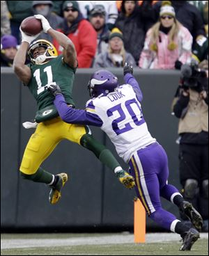 The Packers' Jarrett Boykin catches a pass in front of Minnesota Vikings cornerback Chris Cook during overtime Sunday in Green Bay, Wis. The game ended in a 26-26 tie.