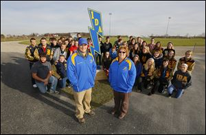 Ida High School track coaches Mike Bolster and Connie DuCharme join their student athletes at the school's old cinder track. The quarter-mile track will be replaced with a synthetic rubberized surface that will enclose the football field and should be complete by the autumn of 2014.
