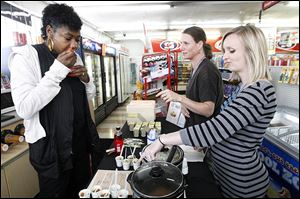 Above, Denise Clark tries homemade apple sauce offered by Stephanie Baltes, right, and Judith Hancock, center, registered dietitians with the Toledo-Lucas County Health Department,  during a kickoff event at a Stop & Go convenience store to highlight healthful food choices.