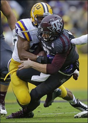 Texas A&M quarterback Johnny Manziel is tackled by LSU defensive end Danielle Hunter in the first half Saturday in Baton Rouge, La.