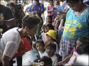 Grammy-winning singer Alicia Keys, left, smiles at a typhoon survivor as she visits the Villamor Air Base in suburban Pasay, south of Manila, Philippines today.