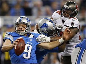 Tampa Bay's Jonathan Casillas, right, grabs ahold of Matthew Stafford during the fourth quarter on Sunday. The Buccaneers harassed Stafford all day, forcing four interceptions.