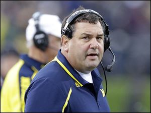 Michigan coach Brady Hoke talks on the sideline during the first half of an NCAA college football game against Northwestern in Evanston, Ill., Saturday, Nov. 16, 2013.