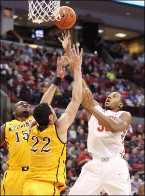 Ohio State's Trey McDonald (55) puts up a shot against Wyoming's Larry Nance, Jr. (22) and Jerron Granberry (15) during the first half.