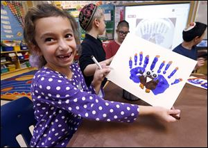 Second-grader Rozie Aronov, 7, holds up a menurkey, a paper-and-paint mashup of a menorah and turkey she created at Hillel Day School in Farmington Hills, Mich., Wednesday. The recent class project reflects one way for Jews in the United States to deal with a rare quirk of the calendar that overlaps Thanksgiving with the start of Hanukkah.