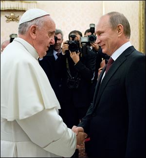 Pope Francis welcomes Russian President Vladimir Putin, right, on the occasion of their private audience at the Vatican today.