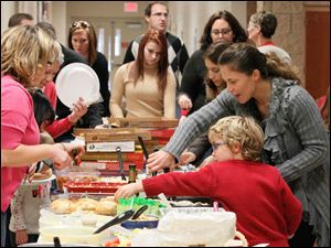 Sam Harshman, 5, front left, and his mom, Suzanne Harshman, getting salad in the meal portion of the celebration.