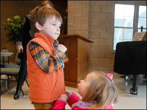 Chase Little, 4, of Sylvania, left, gets help with his zipper from his cousin Cheaney Gabel, 4, of Sylvania Township.