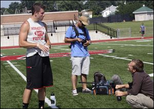 Alex Tanney, left, talks with Daniel Browning Smith, right, and a cameraman from
