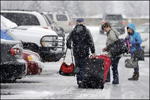 Holiday travelers make their way to their car after arriving at Pittsburgh International Airport in Imperial, Pa. A huge winter storm is expected to have nationwide impact as it causes delays at East Coast airports.