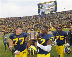 Taylor Lewan, left, and Frank Clark carry the Little Brown Jug after defeating Minnesota. Lewan is a likely first-round NFL pick.