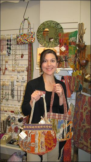 Elizabeth Zilba Baer holds fabric purses made of saris.