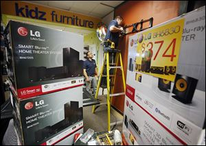 Shawn Manion, on ladder, and Jerry Butte install a Black Friday display Wednesday at the Appliance Center in Maumee.