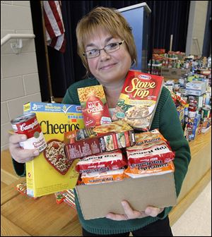 Reka Monus, coordinator for Crossroads Family Resource Center, holds a few of the canned and boxed foods collected for her organization by DeVeaux Elementary School students.