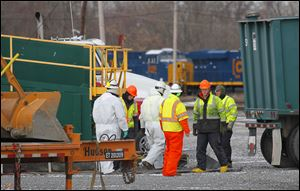 Emergency workers gather near the east end of the CSX train yard in Willard. Immediate cleanup efforts that started early Wednesday did not progress as quickly as hoped. Efforts were slow in part because the substance vaporizes quickly.