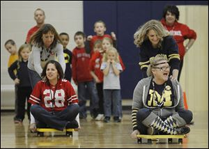DeVeaux Elementary teachers Erin Benner, pushed by Kara Keegan, left, races Nancy Bowman, pushed by Karen Ellis, in an event linked to a food drive for Crossroads Family Resource Center.