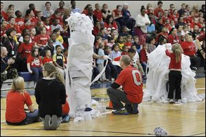 DeVeaux students race to wrap teachers with toilet paper as part of a series of Ohio State-Michigan game week contests, one of which was a food drive for Crossroads Family Resource Center.