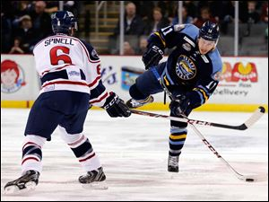 Walleye's Scott Arnold (11) moves the puck against South Carolina's Steve Spinell (6).