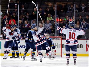 South Carolina's Andrew Cherniwchan (13), center, celebrates scoring a goal against the Walleye.