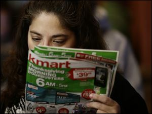 Gretchen Burkhardt looks at a catalog while waiting outside a Kmart store for it to open today in Anaheim, Calif.