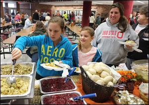 Emilee Gibson, 10, left, her sister Karlee Gibson, 8, mother, Chassity Gibson, and grandmother Rita King, help themselves to Thanksgiving dinner at Willard High School. CSX hired a Columbus catering firm, Concessions by Cox, to make the meal.